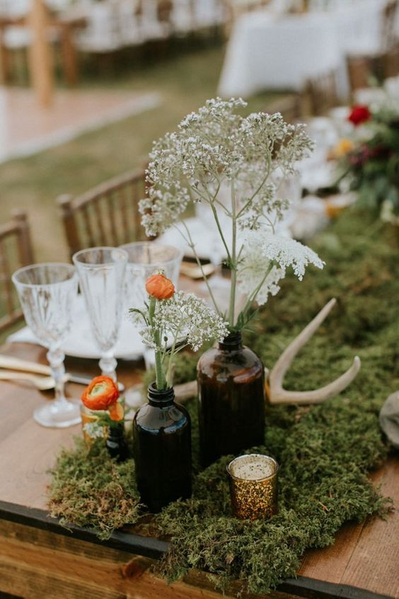a boho wedding centerpiece with moss, apothecary bottles with blooms and wildflowers and candles