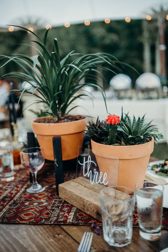 a boho wedding centerpiece with pots with greenery, succulents, a boho table runner and a table number