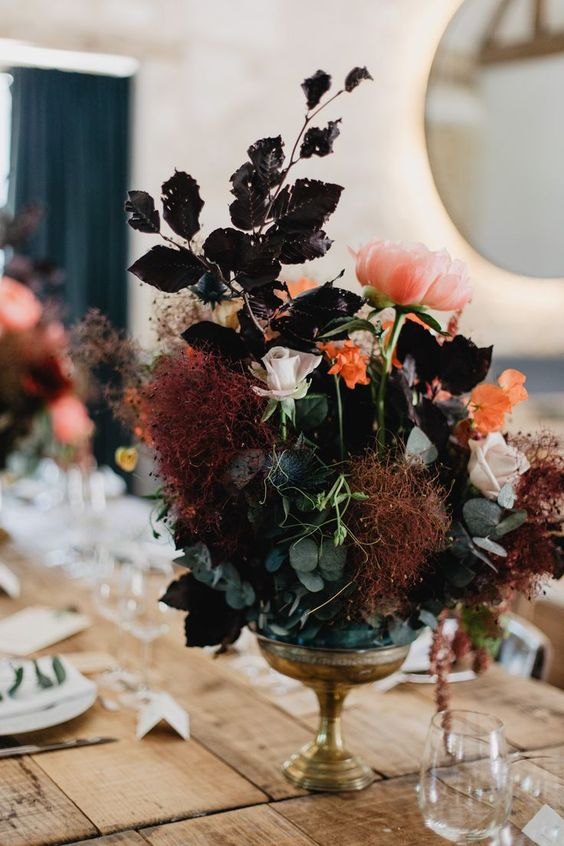 a boo lux wedding centerpiece of green and dark foliage, pink and blush blooms and smokebush