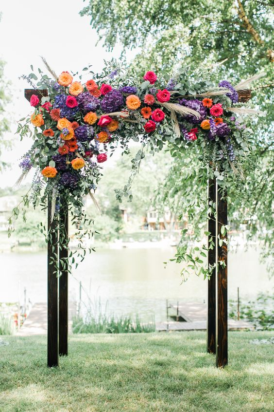 a bright backyard wedding arch of dark stained wood, with greenery, bright blooms, pampas grass is very cool