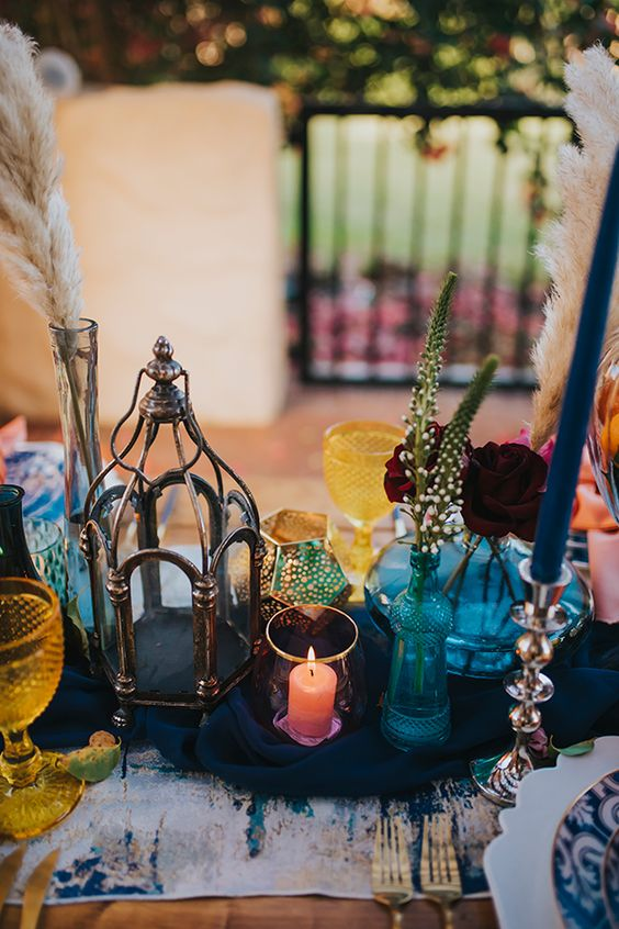 a bright boho Moroccan wedding centerpiece of blue bottles and vases, candle holders and pampas grass
