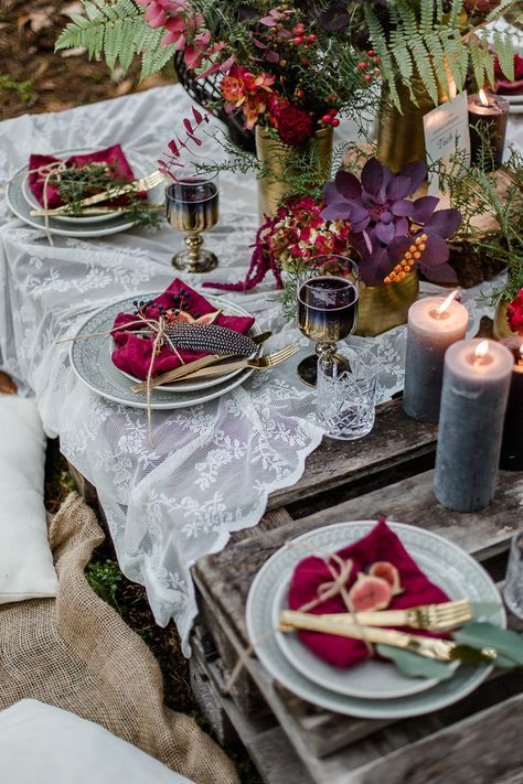 a bright boho meets decadent tablescape with candles, a lace tablecloth, colorful napkins, feathers, greenery and blooms in supmtuous colors