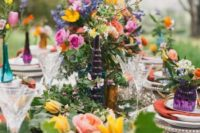 a bright boho spring bridal shower table with greenery, colorful flowers, colorful glasses and vases