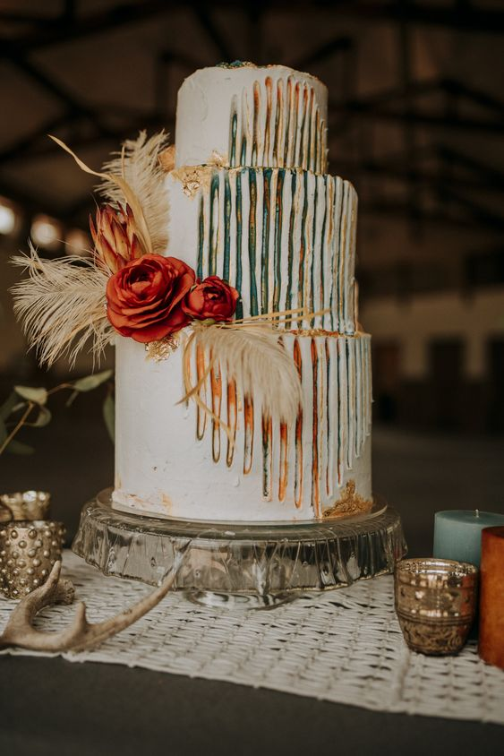 a bright boho wedding cake with catchy colorful detailing and feathers and bright blooms for a boho wedding
