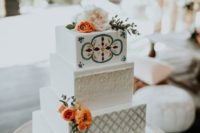 a bright boho wedding cake with various geometric and wood tiers, colorful patterns, bright blooms and greenery