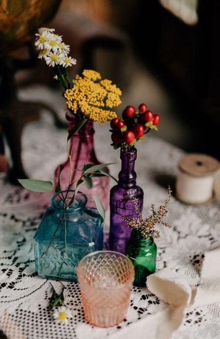 a bright boho wedding centerpiece of jewel tone bottles, wildflowers and greenery for a summer boho wedding