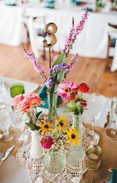 a bright boho wedding centerpiece with bold blooms, greenery, a wooden table number and a doily
