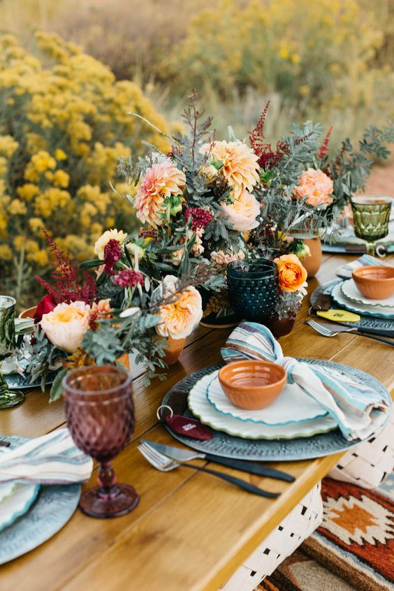 a bright boho wedding tablescape with blue plates and chargers, bowls, lush florals and colored glasses