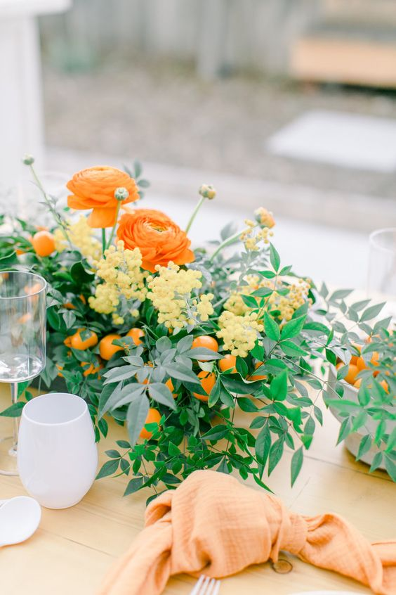 a bright spring bridal shower centerpiece with orange and yellow blooms, greenery and kumquats