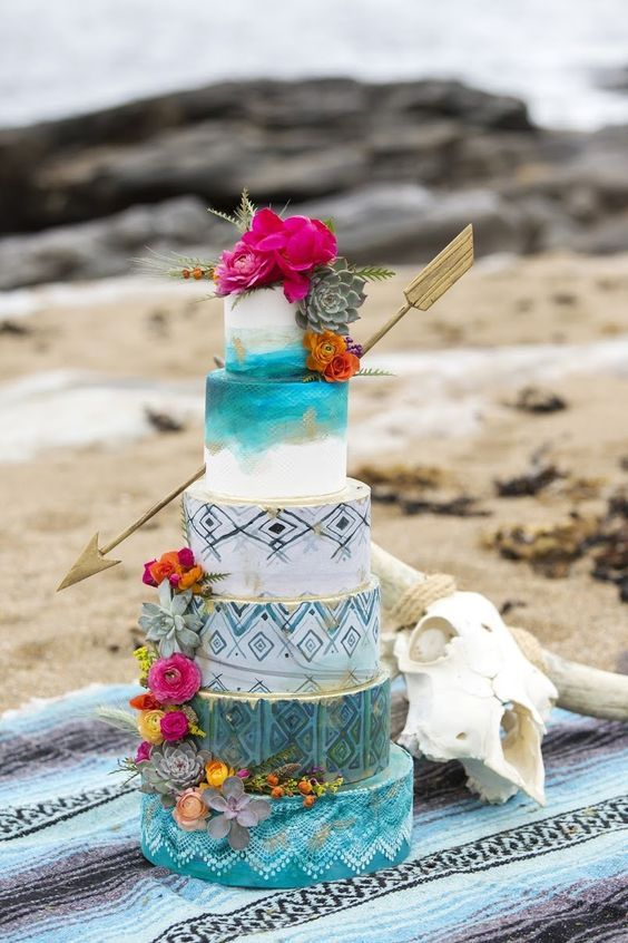 a bright turquoise wedding cake with tribal patterns, ombre, gold leaf, bright blooms and succulents and a large arrow