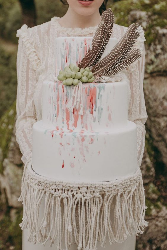 a bright watercolor wedding cake with succulents and feathers plus real macrame for plate decorating
