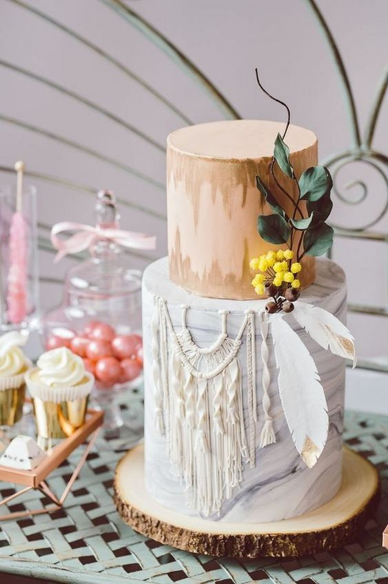 a catchy boho wedding cake with an ikat tier and a sugar macrame one plus some feathers with gold edges and sugar berries and leaves