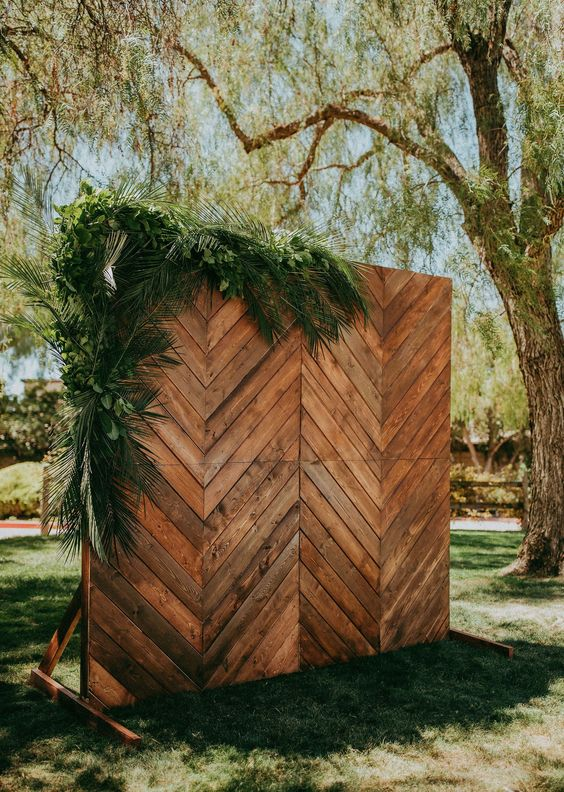 a chevron stained wood wedding backdrop decorated with greenery is a cool and easy to realize idea for a backyard wedding