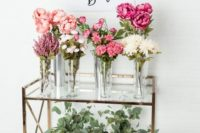 a chic and modern flower bar with pink and white blooms and greenery to make your own bouquet