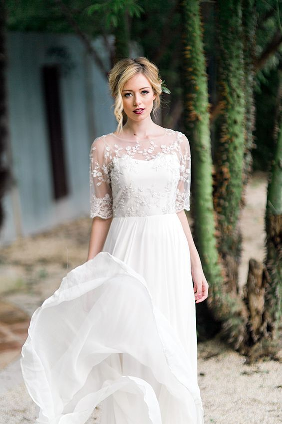 a chic empire waist wedding dress with a pleated skirt and a sheer lace and embellished coverup with short sleeves