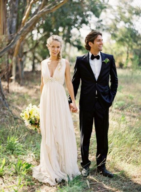 a chic empire waist wedding dress with a plunging neckline, no sleeves, a draped bodice and skirt for a casual bride