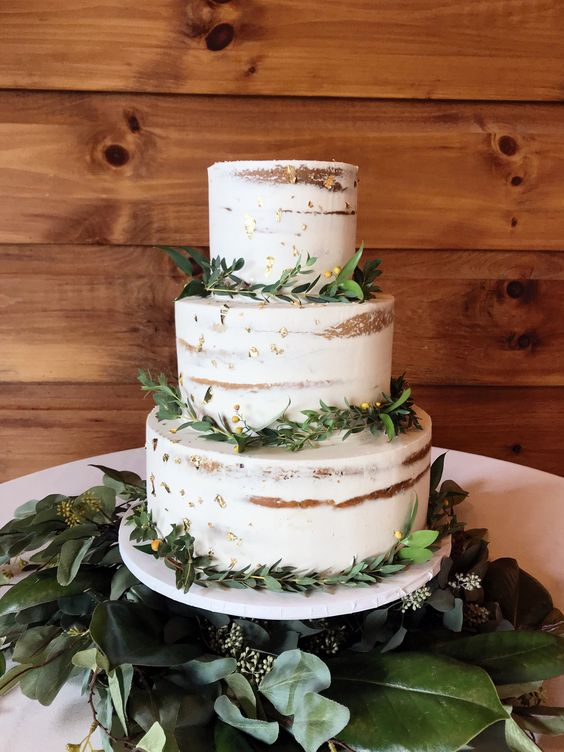 a chic naked wedding cake with gold leaf and greenery is a cool piece for many weddings, not only a rustic one
