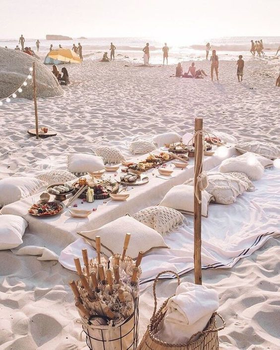a chic neuutral boho beach picnic setting with crochet pillows, a white tablecloth and lots of food