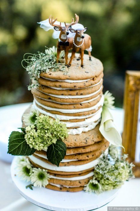a chocolate chip cookie wedding cake with creamy filling, greenery and funny deer toppers