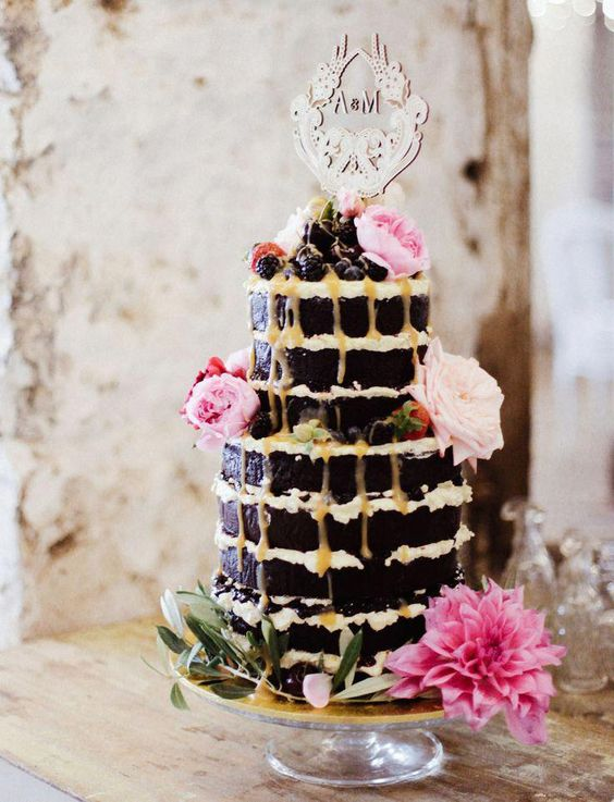 a chocolate wedding cake with honey drip, fresh blooms and greenery and berries on top for a summer boho wedding