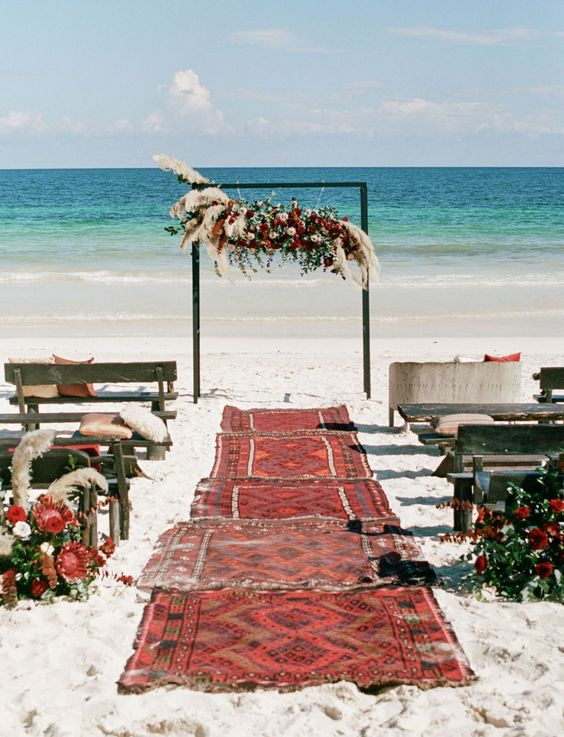 a colorful boho beach ceremony space with boho rugs, colorful blooms, greenery, pampas grass and an oversized floral installation