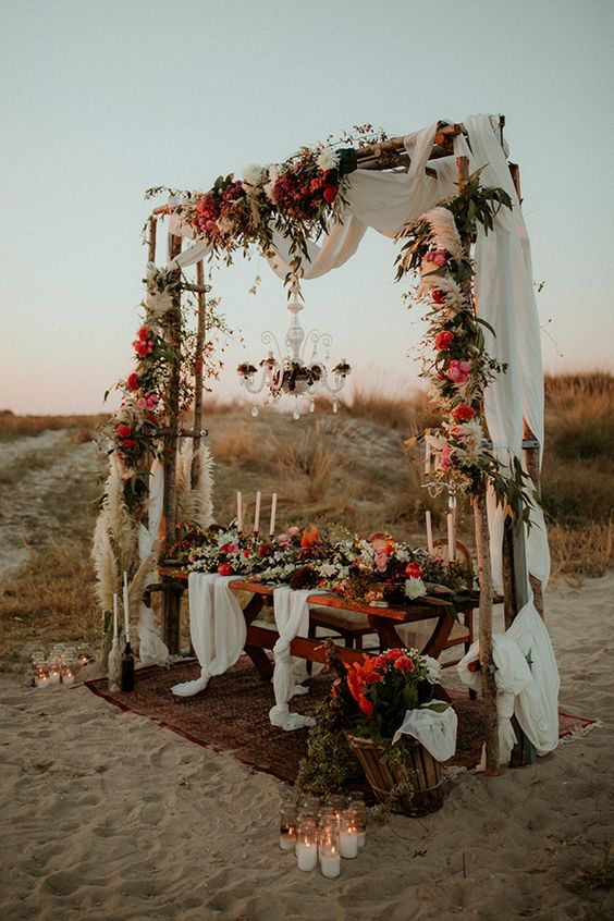 a colorful boho beach wedding reception space with colorful blooms and pampas grass, a crystal chandeliet, airy runners and lots of candles