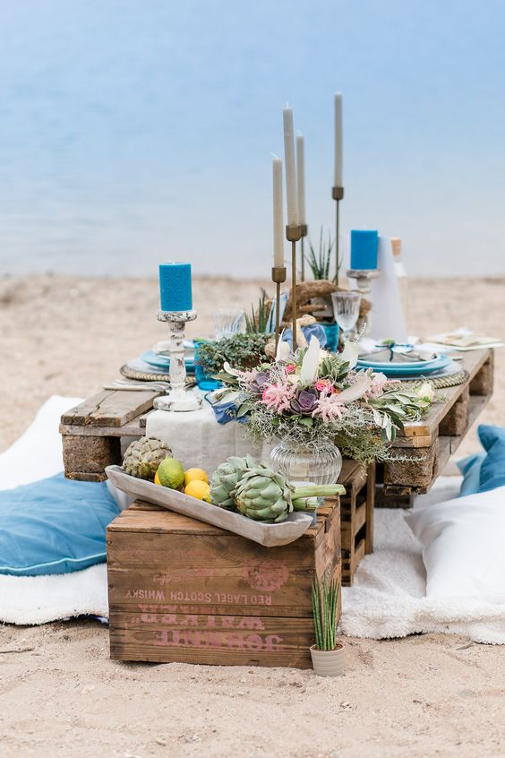 a colorful boho beach wedding tablescape with blue candles and pillows, a textural floral arrangements and air plants