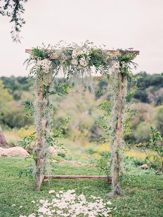a cool rustic wedding arch with greenery and white blooms, white petals on the ground is ideal for a backyard wedding