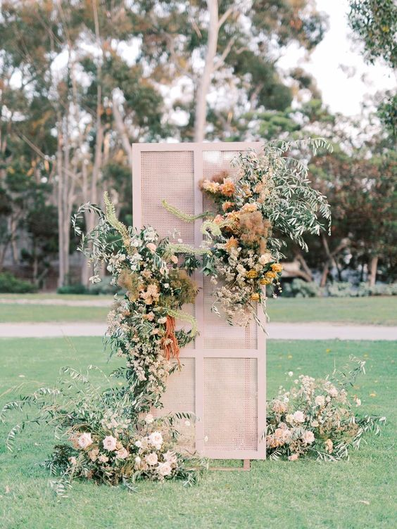 a creative backyard wedding backdrop with neutral and pastel blooms and greenery plus dried foliage