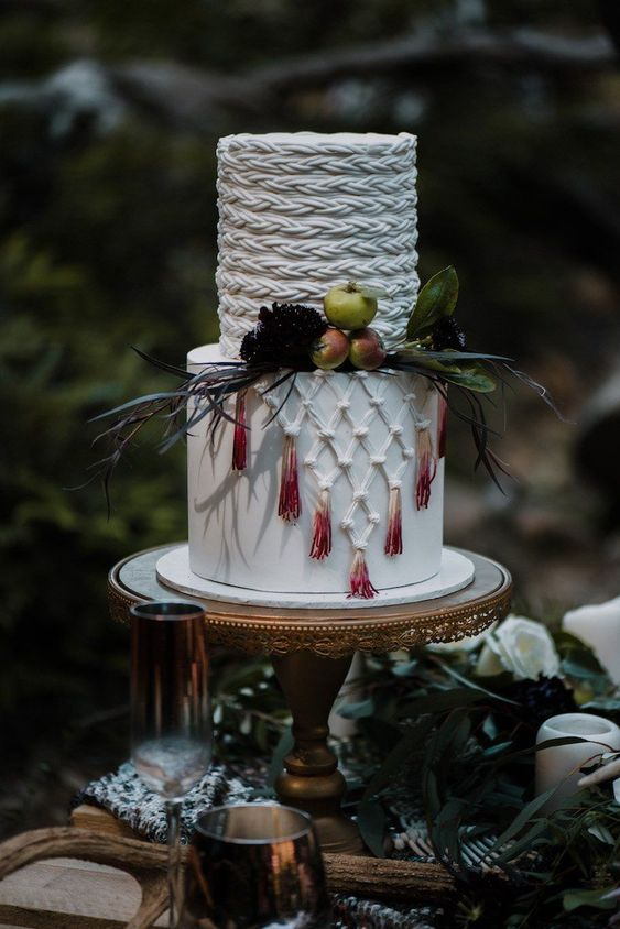 a creative wedding cake with sugar macrame decor and dip dyed tassels plus greenery and little apples for a boho wedding