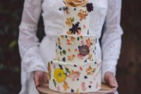 a cute and bold floral wedding cake with sugar and real petals and dried blooms plus fresh ones on top for a flower child wedding