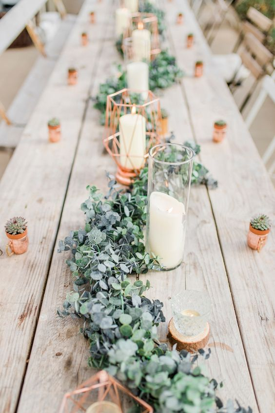 a cute greenery and foliage table runner with candles and copper canlde holders is a chic idea
