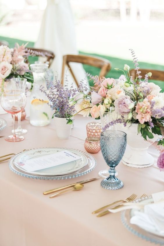 a cute pastel bridal shower tablescape with pink linens, pink, white blooms and lavender, blue and pink glasses