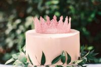 a cute pink bridal shower cake with a sugar crown and greenery is amazing for spring