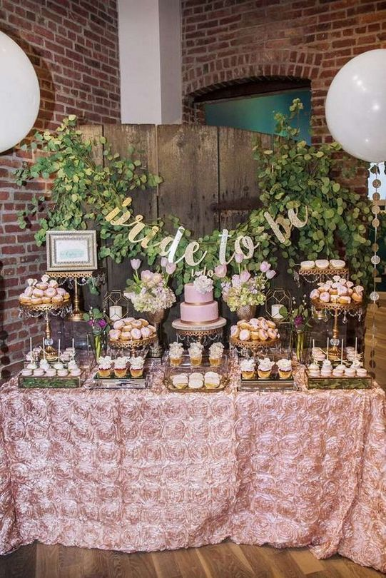 a cute pink spring bridal shower dessert bar done with greenery, calligraphy and pink blooms