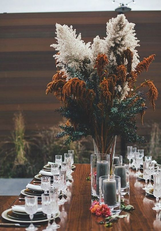 a dimensional and textural wedding centerpiece of greenery, dried and rust blooms for a boho wedding