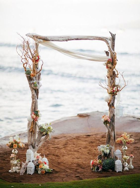 a driftwood wedding arch with peach and white blooms, seashells and succulents plus candle lanterns