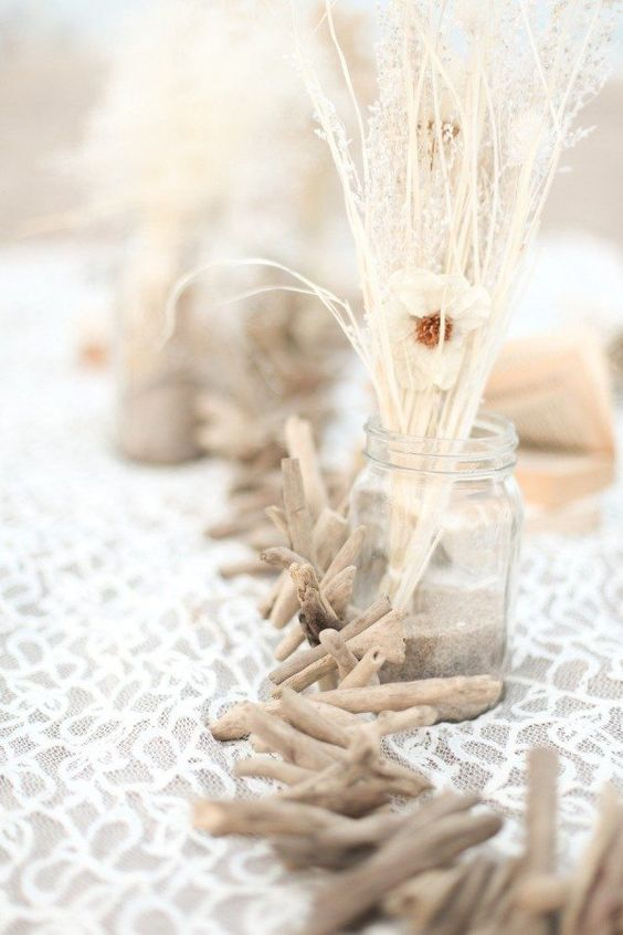 a driftwood wedding centerpiece of a garland, some lace and dried herbs plus blooms for a beach wedding