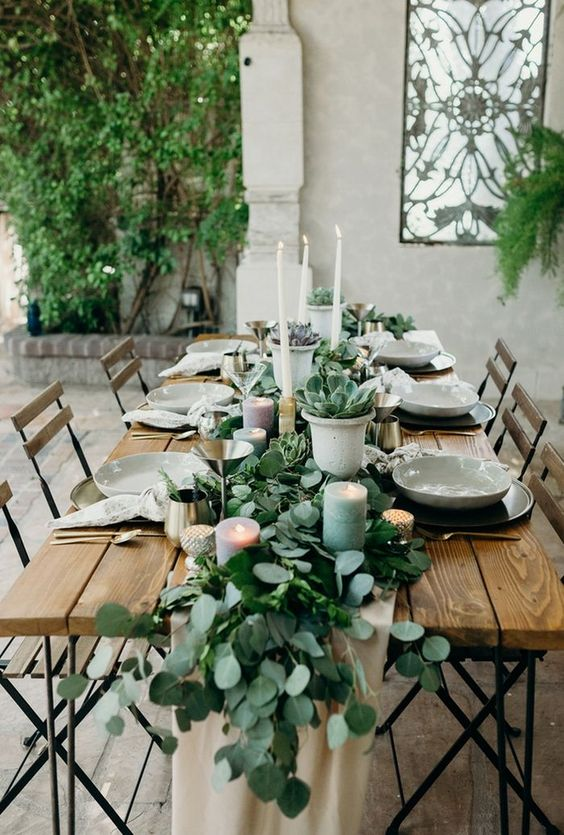 a eucalyptus table runner with succulents in pots, with pastel candles and tall white ones is super chic and edgy