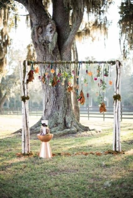 a fall boho wedding arch with bright blooms and fall leaves hanging down, with a metallic table next to the arch