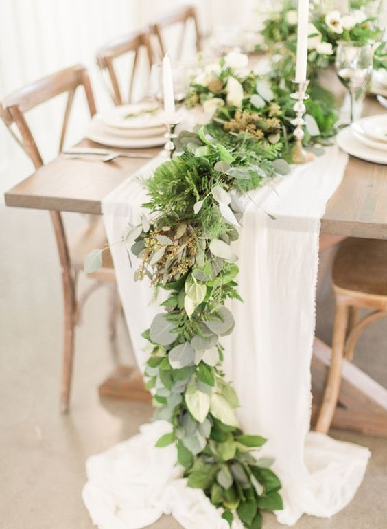 a fern and eucalyptus wedding table runner combined with a white fabric one and spruced up with gold candle holders