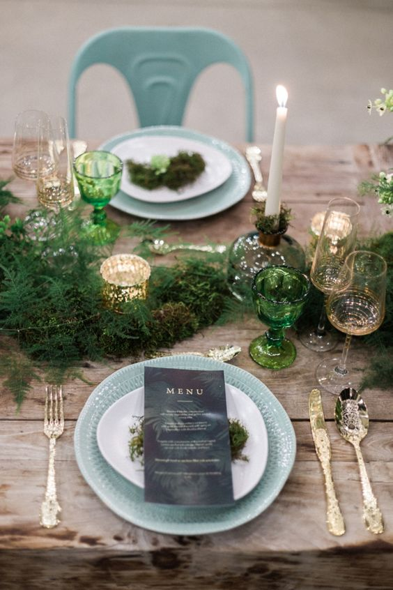 a fern tablr runner, tall candles and green glasses and mercury glass candle holders on an uncovered table