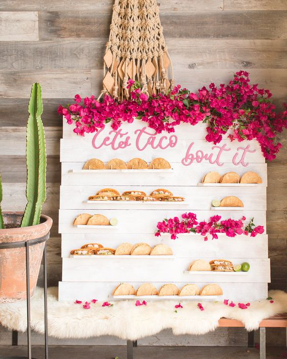 a fun taco wall decorated with faux fur and fuchsia blooms and greenery for a bright pink spring shower