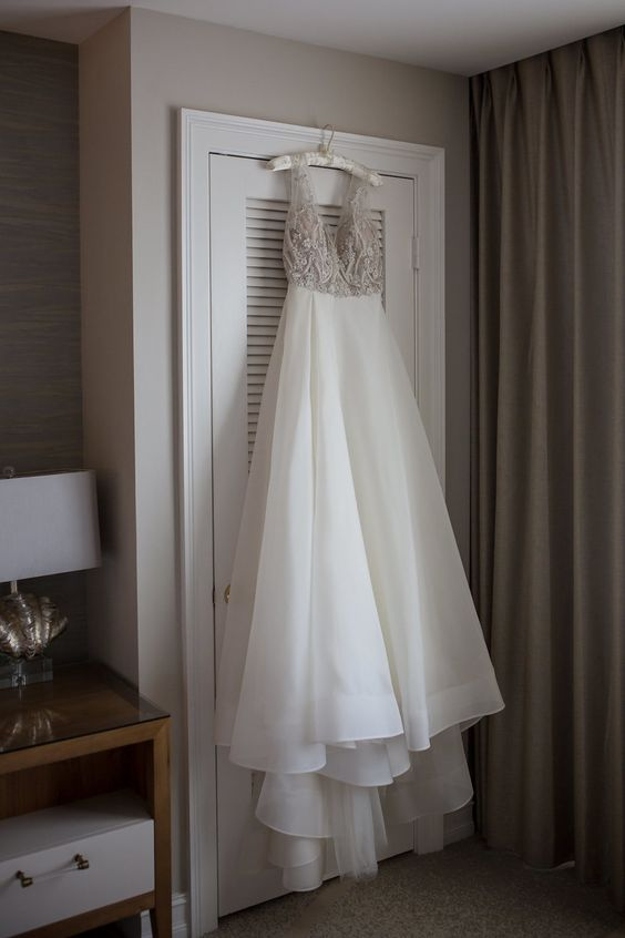 a gorgeous A-line wedding dress with a silver embellished bodice with a deep neckline and a layered skirt with a train