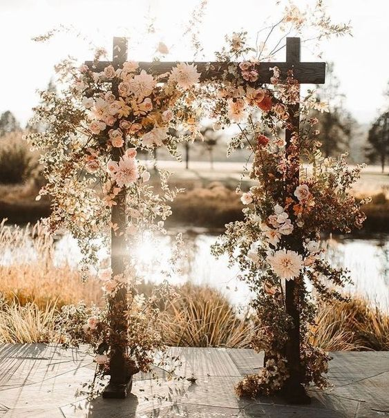 a gorgeous rustic wedding arch decorated with white and blush blooms, with greenery and dried foliage for a fall backyard wedding