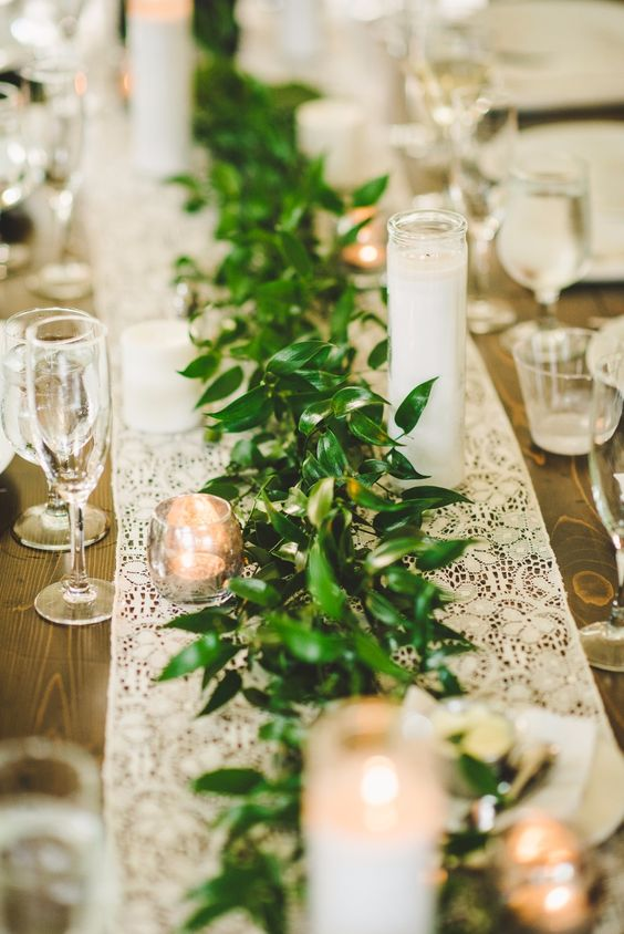 a greenery table runner with a white lace one underneath looks very neat and elegant