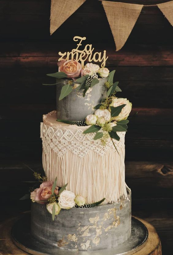 a grey and white wedding cake with gold leaf, macrame detailing, whiet and pink blooms, greenery and a gold topper