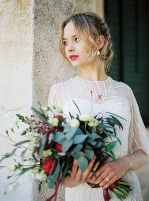 a heavily embellished wedding dress with a botanical pattern and wide sleeves