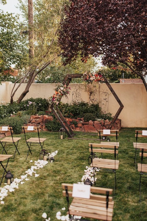 a hexagon backyard wedding arch decorated with greenery and bright blooms, petal to line up the aisle and simple wooden chairs