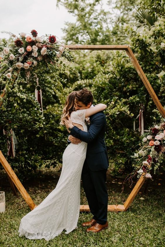 a hexagon wedding arch decorated with greenery, dark and pastel blooms and a dream catcher is a lovely idea for a fall backyard wedding